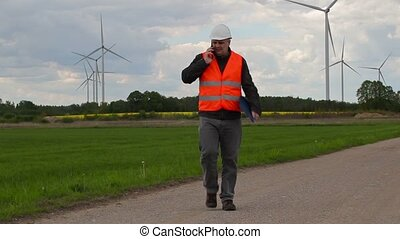 Electrician engineer walking and talking on smart phone near...