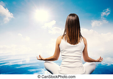 Young woman meditating at lake - Close up rear view of young...