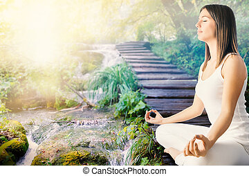Girl meditating next to stream in forest - Close up side...