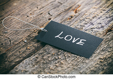 "Closeup of pricing tag with twine and ""Love"" text on wooden..."