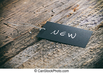 "Closeup of pricing tag with twine and ""New"" text on wooden..."
