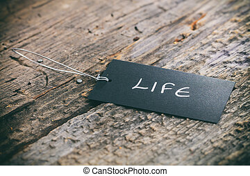 "Closeup of pricing tag with twine and ""Life"" text on wooden..."