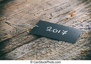"Closeup of pricing tag with twine and ""2017"" text on wooden..."
