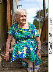 Old woman sitting on the porch