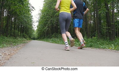 Happy couple jogging in the park, slow motion