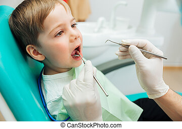 Boy sitting with mouth opened during oral checkup at dentist...