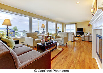 Nicely furnished living room with polished hardwood floor and water view