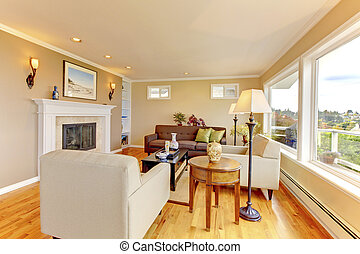 Bright cozy living room with beige walls and fireplace -...