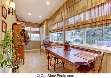 Bright sunroom with many windows on the back of the house. -...