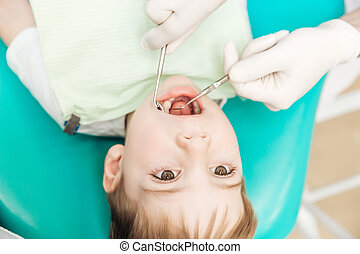 Boy with mouth opened during oral inspection in dental...
