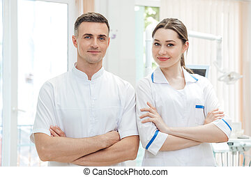 Portrait of a confident male and female dentists smiling at...