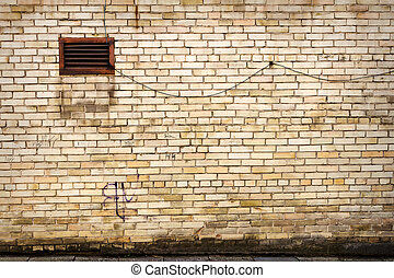 Yellow brick wall with one small window