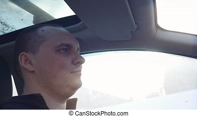 Man sitting and driving in the car under sunset sky in...