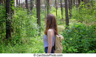 Young girl with a backpack walking along the road in the...