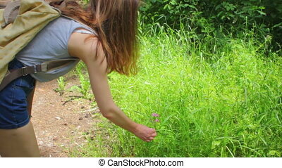 Young girl on a walk in the woods, smelling a flower.