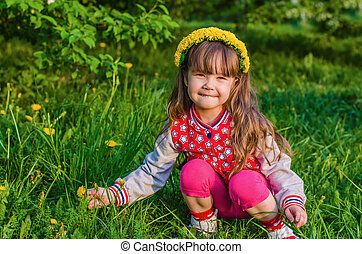 Beautiful little girl picking flowers
