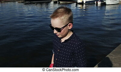 baby boy blond 8 years in a blue shirt, light trousers