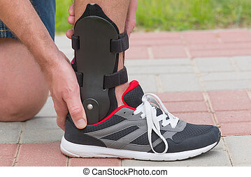 Man wearing ankle brace - Man in athletic sneakers checking...