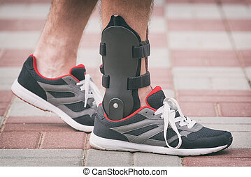 Man wearing ankle brace - Man in athletic sneakers wearing...