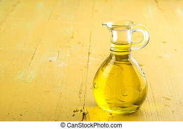 Extra virgin olive oil glass jars on yellow wooden table