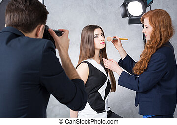 Backstage of a studio beauty session - Female model posing...