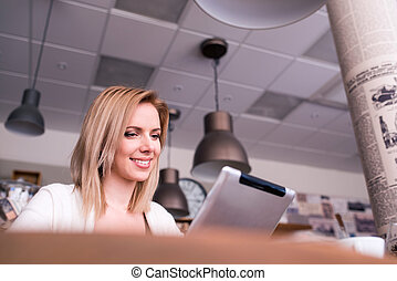 Blond woman with tablet in cafe, reading - Blond woman with...