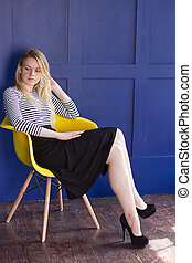 Blond girl in skirt and vest sits on a chair