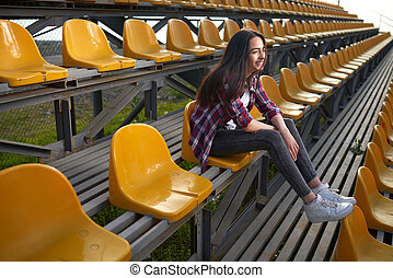 beautiful lonely woman sitting on tribunes and laughs Side...
