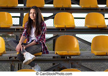 lonely teen girl sitting on tribunes, front view