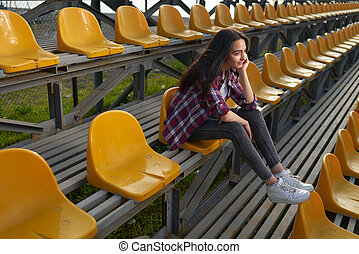 beautiful lonely woman sitting on tribunes and smiles Side...