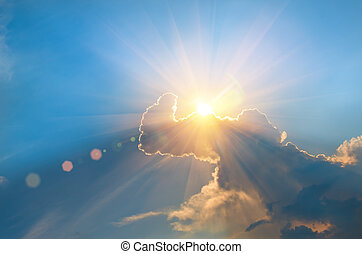 The sun behind the clouds in a blue sky