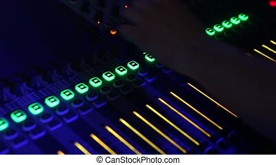 Professional DJ at work during a show with flashing light. Sound engineer working in a club with a sound console and microphones