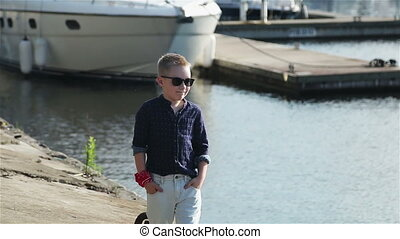 boy blond 8 years in a blue shirt, light trousers