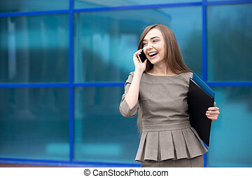 Portrait of business woman laughing while talking on mobile...