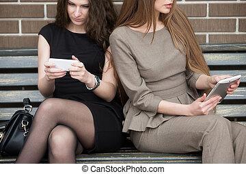 Two young beautiful women sitting on bench - Two beautiful...