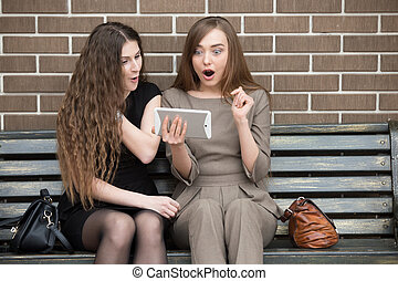 Young beautiful women looking at tablet screen in shock -...