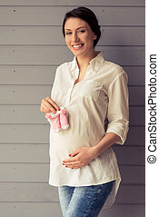 Beautiful pregnant woman is holding baby shoes, keeping one...