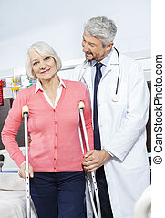 Senior Patient Being Helped By Doctor With Crutches -...
