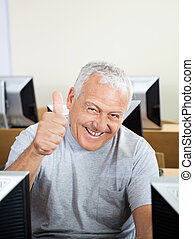 Smiling Senior Man Gesturing Thumbs Up In Computer Class