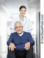 Smiling Female Doctor Pushing Senior Patient In Wheel Chair