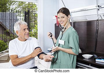 Confident Nurse Examining Blood Pressure Of Senior Man