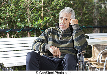 Thoughtful Senior Male Patient Sitting In Wheelchair At Lawn...
