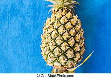 top of fresh pineapple on blue background.