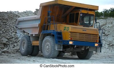 Heavy mining dump trucks driving along the opencast