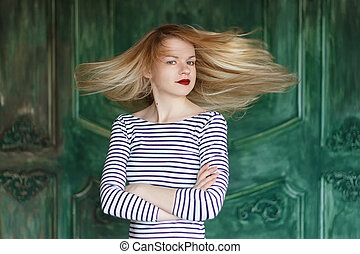 Blonde with red lips in striped shirt on a green background...