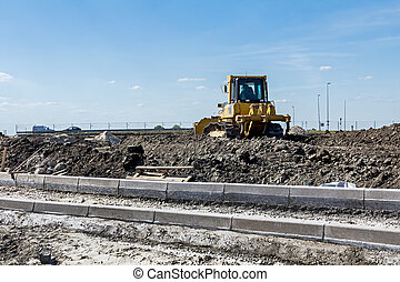 Bulldozer machine is leveling construction site
