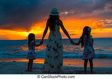 Family silhouette in beautiful sunset at the beach