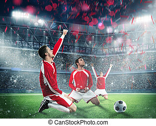 Win a football game - Soccer players exults on a stadium...