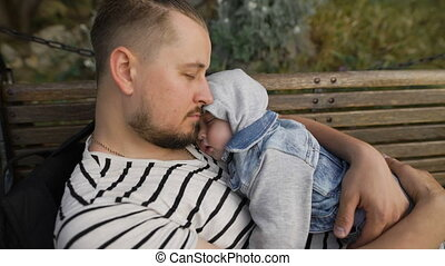 Dad and little son rest in the park on a bench.