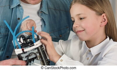 Nice girl constructing robot toy with her father - Like this...